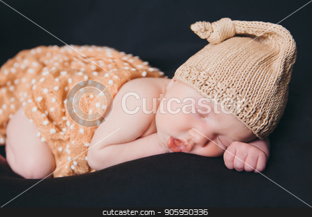 A little child in a beige cap lies on tje black background stock photo, A little child in a beige cap lies on tje black background by aaalll3110