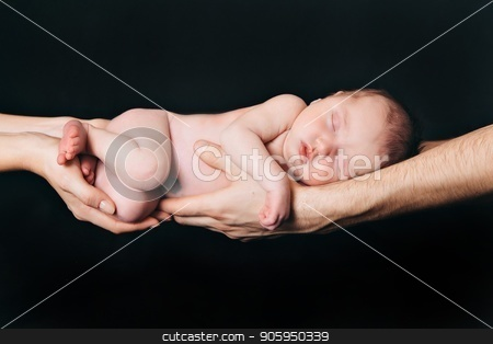 newborn baby lying on the hands of parents on a black background. Imitation of a baby in the womb. stock photo, newborn baby lying on the hands of parents on a black background. Imitation of a baby in the womb. by aaalll3110