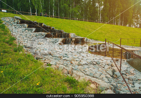 Water flows down the stone steps among the green grass stock photo, Water flows down the stone steps among the green grass by aaalll3110