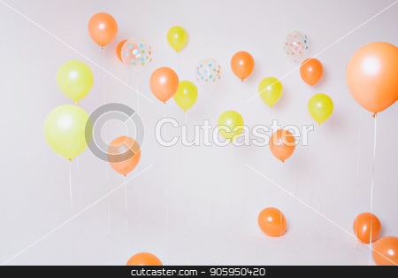 party decoration concept - colorful air yellow and orange balloons on white wall background stock photo, party decoration concept - colorful air yellow and orange balloons on white wall background by aaalll3110