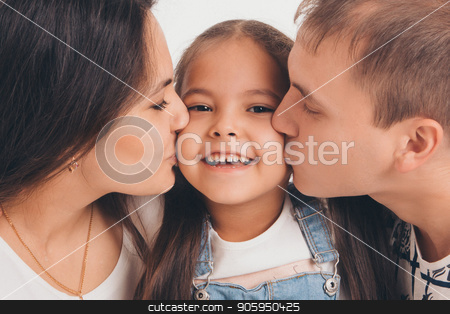 Portrait of a girl who holds her parents ' hands on a white background. Mother and father kiss their daughter stock photo, Portrait of a girl who holds her parents ' hands on a white background. Mother and father kiss their daughter by aaalll3110