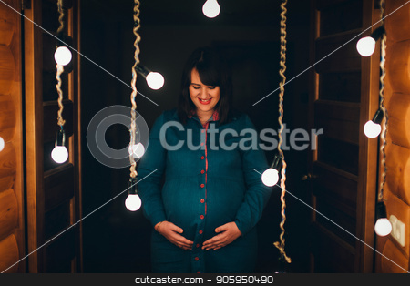 a pregnant woman holds her hands on her stomach against the background of burning light bulbs stock photo, a pregnant woman holds her hands on her stomach against the background of burning light bulbs by aaalll3110