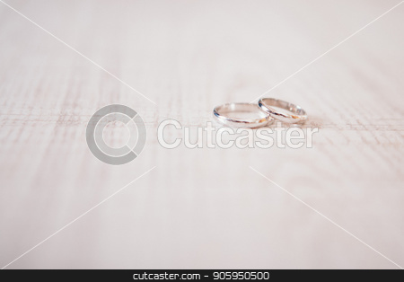 Two gold rings on wooden surface. wedding rings on a light background stock photo, the background for the wedding. suitable for advertising jewelry by aaalll3110
