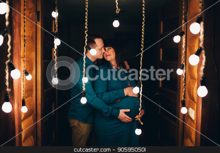 Man hugs his pregnant woman on a lamps background stock photo, Man hugs his pregnant woman on a lamps background by aaalll3110