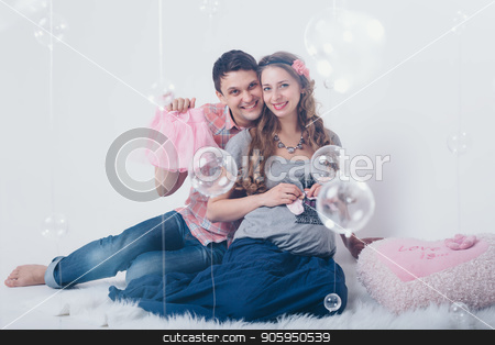 pregnant woman and ,man playing with rattle on floor on white background stock photo, pregnant woman and ,man playing with rattle on floor on white background by aaalll3110