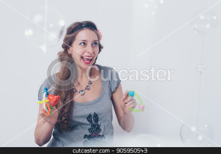 pregnant woman playing with rattle on floor on white background