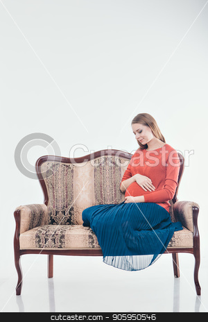 Pregnant woman sitting on the couch in a white background stock photo, Pregnant woman sitting on the couch in a white background by aaalll3110