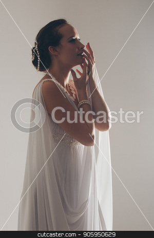 girl in white and with raised hands, attached to the floor dresses. the bride in a dress in Greek style. brunette in pearl jewelry lowered her head. stock photo, girl in white and with raised hands, attached to the floor dresses. the bride in a dress in Greek style. brunette in pearl jewelry lowered her head. by aaalll3110