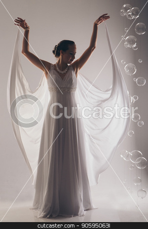 girl in white and with raised hands, attached to the floor dresses. the bride in a dress in Greek style. brunette in pearl jewelry lowered her head. The woman looks like a bird or a bat stock photo, girl in white and with raised hands, attached to the floor dresses. the bride in a dress in Greek style. brunette in pearl jewelry lowered her head. The woman looks like a bird or a bat by aaalll3110