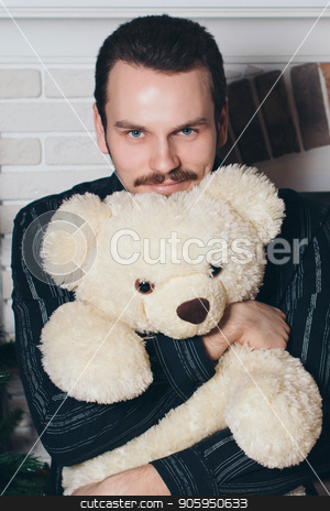 A man in a black shirt hugs a Teddy bear. Beautiful brunette holding a toy stock photo, A man in a black shirt hugs a Teddy bear. Beautiful brunette holding a toy by aaalll3110