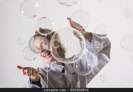 A mad scientist is experimenting with glass balls. A woman in a white robe smiles strangely and stretches her arms forward. The blonde is trying to hug someone stock photo, A mad scientist is experimenting with glass balls. A woman in a white robe smiles strangely and stretches her arms forward. The blonde is trying to hug someone. Photo for fans of physics and chemistry. Glass balls in the foreground, behind white background by aaalll3110