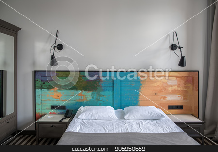 Stylish hotel room stock photo, Beautiful room in a hotel with light walls and striped floor. There is a blue double bed with a colorful wooden bedhead, dark gray nightstands, black lamps on the wall, wardrobe with a mirror. by bezikus