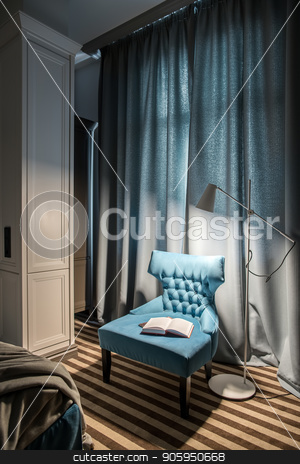 Stylish hotel room stock photo, Elegant hotel room with light walls and a striped floor. There is a window with drawn curtains, blue armchair with a book, luminous white floor lamp and a blue bed with a gray coverlet. Vertical. by bezikus