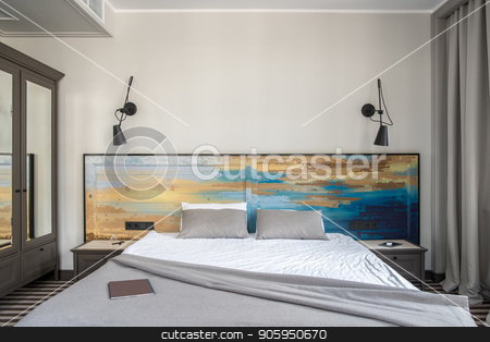 Stylish hotel room stock photo, Comfortable hotel room with light walls and a striped floor. There is a double bed with a colorful wooden bedhead, dark gray nightstands and a wardrobe with mirrors, black lamps on the wall. by bezikus