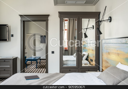 Beautiful hotel room stock photo, Stylish hotel room with light walls and a striped floor. There is a double bed with a colorful wooden bedhead, dark gray wardrobe with mirrors, stand, black lamps on the wall, blue table, TVs. by bezikus