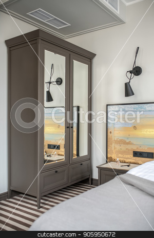 Stylish hotel room stock photo, Nice hotel room with light walls and a striped floor. There is a bed with a colorful wooden bedhead, dark gray wardrobe with mirrors, nightstand with accessories, black lamp on the wall. Vertical. by bezikus