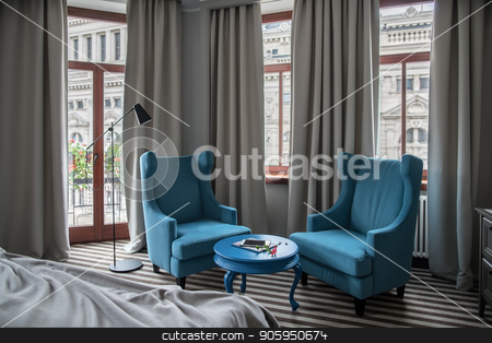 Stylish hotel room stock photo, Hotel room with light walls and a striped floor. There is a round blue table with two armchairs, windows with curtains, door to the balcony, dark floor lamp, bed and a stand. Horizontal. by bezikus