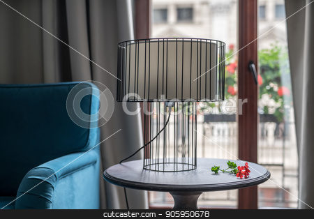 Stylish hotel room stock photo, Metal lamp with a light lampshade on the round wooden table on the background of the glass door to the balcony in the hotel room. There is a blue sofa on the right side and a red flower near the lamp. by bezikus