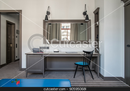 Stylish hotel room stock photo, Contemporary hotel room with light walls and a striped floor. There is a blue table, wide table with a chair, different lamps, mirror on the wall, shelves with decorations, doors. Horizontal. by bezikus
