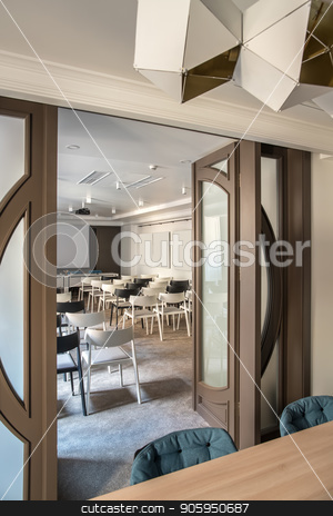 Modern conference hall stock photo, Big conference hall with white walls and a gray floor. There are many light and dark chairs, board, projector, wooden table with soft chairs, wide door, hanging fancy lamps. Vertical. by bezikus