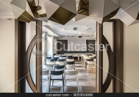 Big conference hall stock photo, Modern conference hall with white walls and a gray floor. There are many light and dark chairs, board, projector, tables with soft chairs, wide door, hanging fancy lamps. Horizontal. by bezikus