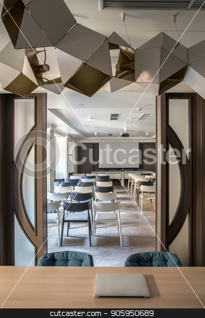 Modern conference hall stock photo, Contemporary conference hall with white walls and a gray floor. There are many light and dark chairs, board, projector, tables with soft chairs, wide door, hanging fancy lamps. Vertical. by bezikus