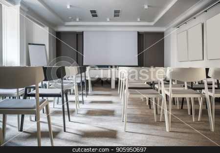 Modern conference hall stock photo, Beautiful conference hall with white walls and a gray floor. There are many light and dark chairs, boards, tables with blue chairs, lamps, window. Horizontal. by bezikus