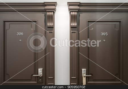Stylish interior in hotel stock photo, Two brown doors with room numbers on them on the light wall background in the hotel. Closeup horizontal photo. by bezikus
