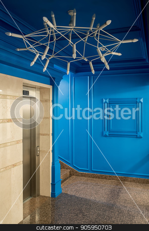 Stylish interior in hotel stock photo, Cool interior in a hotel with blue walls and a tiled floor. There is a stair, lift, big light chandelier. Vertical. by bezikus
