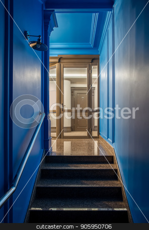 Stylish interior in hotel stock photo, Illuminated interior in the hotel with blue and light walls and a tiled floor. There is a stair with a handrail, glass entrance, brown door with a room number, hanging lamp on the wall. Vertical. by bezikus