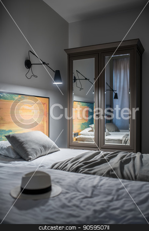 Stylish hotel room stock photo, Luminous room in a hotel with light walls. There are two beds with a colorful wooden bedhead, black lamps on the wall, window with curtains, nightstand, dark gray wardrobe with mirrors. Vertical. by bezikus