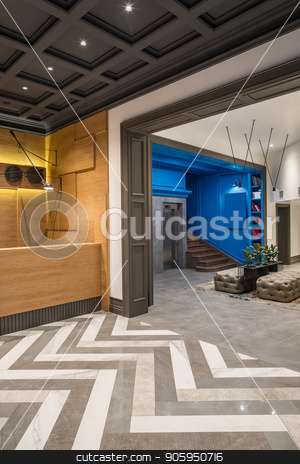 Stylish interior in hotel stock photo, Contemporary hallway in the hotel with different walls and a tiled floor. There is a wooden reception desk, lift, brown stair, shelves with books, black stand with plants, sofas, luminous lamps. by bezikus