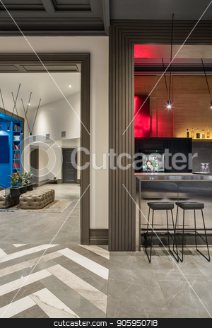 Stylish interior in hotel stock photo, Modern hallway and a bar in a hotel with light walls and a tiled floor. There is a glossy bar rack with black chairs, sofas, stand with plants in the pots, doors, luminous lamps. Vertical. by bezikus