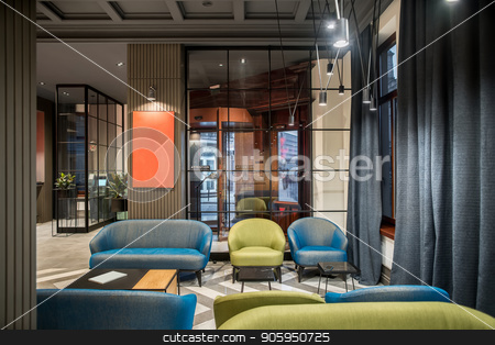 Stylish interior in hotel stock photo, Luminous interior in the hotel with dark ceiling and patterned tiled floor. There is a glass entrance door, multicolored armchairs and sofas, tables, glass partitions, columns, green plants, lamps. by bezikus