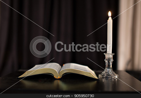 Education concept. Close-up view of old burning candle with shabby old book on wooden background. Focus on the candle stock photo, Education concept. Close-up view of old burning candle with shabby old book on wooden background. Focus on the candle by aaalll3110