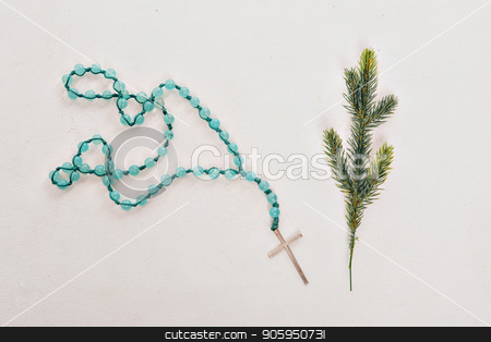Spruce branch and wooden cross on blue beads on white background stock photo, Spruce branch and wooden cross on blue beads on white background by aaalll3110