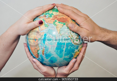 Four hands holding globe on white background. The globe is in the palm stock photo, Four hands holding globe on white background. The globe is in the palm by aaalll3110