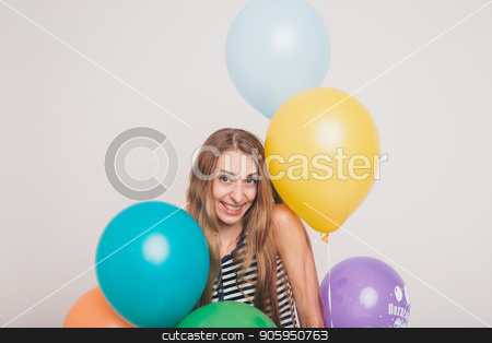 blonde girl smiling and looking at camera between multicolored balls on white background. Studio portrait of attractive girl waiting for birthday party. Face and balloons stock photo, blonde girl smiling and looking at camera between multicolored balls on white background. Studio portrait of attractive girl waiting for birthday party. Face and balloons by aaalll3110
