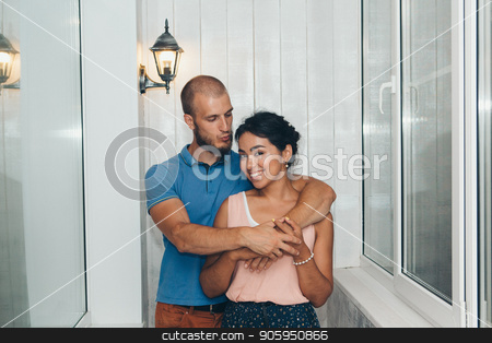 Family portrait of husband and wife. The pair on the balcony. European hugs Asian. Man and woman smiling stock photo, Family portrait of husband and wife. The pair on the balcony. European hugs Asian. Man and woman smiling by aaalll3110