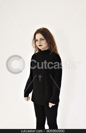 Girl with bright makeup in black suit and with cross on chest on white wall background. Pretty woman in black clothes. Young woman with black lips and red hair stock photo, Girl with bright makeup in black suit and with cross on chest on white wall background. Pretty woman in black clothes. Young woman with black lips and red hair by aaalll3110