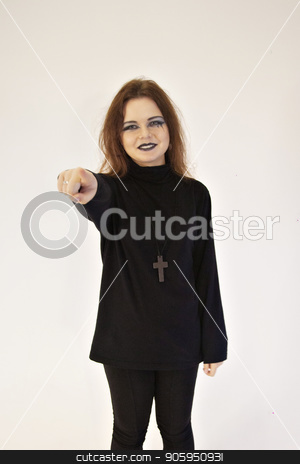 Girl with bright makeup wearing a black suit and a cross on his chest points a finger at the white background of the wall. A young woman with black lips pulled her hand forward stock photo, Girl with bright makeup wearing a black suit and a cross on his chest points a finger at the white background of the wall. A beautiful brunette shows with her finger. A young woman with black lips pulled her hand forward by aaalll3110