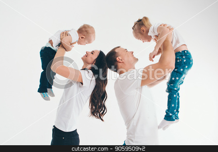 family portrait on the floor on white background. parents hold children in their arms.A man and a woman lifted a boy and a girl up stock photo, family portrait on the floor on white background.parents hold children in their arms.A man and a woman lifted a boy and a girl up by aaalll3110