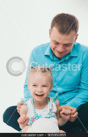 A man with a child in a white background. Father and daughter in blue stock photo, A man with a child in a white background. Father and daughter in blue by aaalll3110