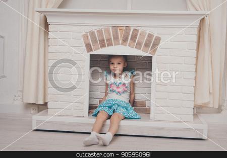 a little girl in a dress sitting inside the fireplace stock photo, a little girl in a dress sitting inside the fireplace by aaalll3110