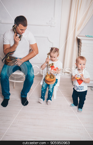 family portrait: father and two children. Business situation: telephone conversations. A man, a boy, a girl sit in a line stock photo, family portrait: father and two children. Business situation: telephone conversations. A man, a boy, a girl sit in a line by aaalll3110