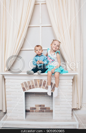 a little girl and a guy in a dress sitting by the fireplace. Family portrait: sister and brother stock photo, a little girl and a guy in a dress sitting by the fireplace. Family portrait: sister and brother by aaalll3110