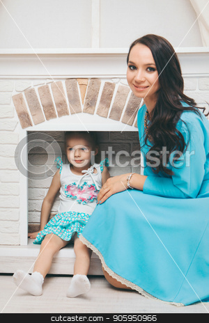 a little girl and a woman in a dress sitting by the fireplace. Family portrait: mother and daughter stock photo, a little girl and a woman in a dress sitting by the fireplace. Family portrait: mother and daughter by aaalll3110