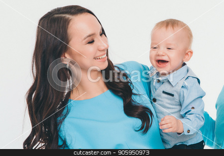 a woman in a blue dress holding a baby in a blue shirt against a white wall. The mother took his son in his arms. Brunette and her babe stock photo, a woman in a blue dress holding a baby in a blue shirt against a white wall. The mother took his son in his arms. Brunette and her babe by aaalll3110