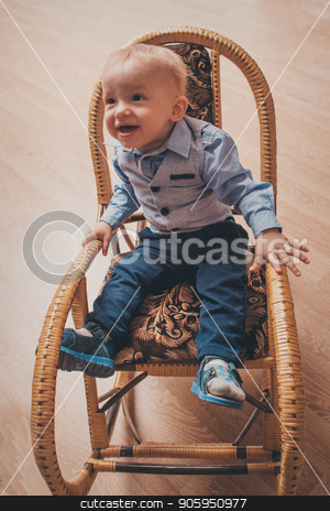 the little boy sits in a bamboo chair stock photo, the little boy sits in a bamboo chair by aaalll3110