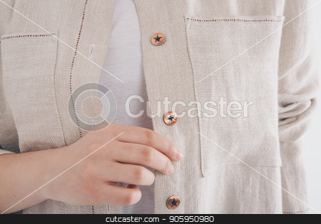 cropped photo: girl holding her hand near her face. Model posing in a white cloth. Item of clothing close-up stock photo, cropped photo: girl holding her hand near her face. Model posing in a white cloth. Item of clothing close-up by aaalll3110